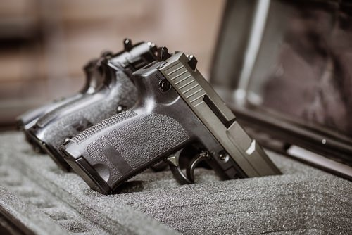 guns laying on top of container - per Penal Code 25610 PC, firearms transported in a vehicle in California must be in a locked container