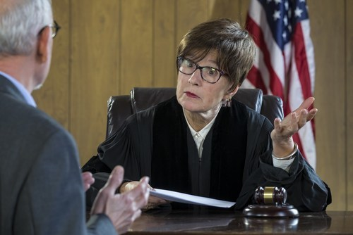 female judge listening to male lawyer