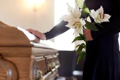woman holding bundle of lilies next to casket - a survivor action can help surviving families recover damages after the wrongful death of a loved one