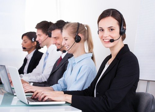 Team of five receptionists with laptops and headsets