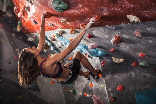 Young woman clinging upside down to indoor rock climbing wall