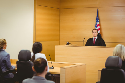 Judge presiding over a courtroom - California Penal Code 1377 allows prosecutors and judges to dismiss charges as part of a civil compromise