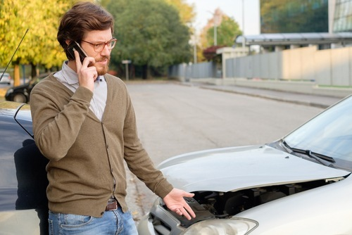 young man on cell phone after car accident