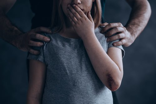 man placing his hands on the shoulders of a young girl