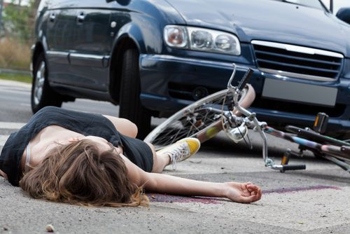 woman on ground after crash between car and bike