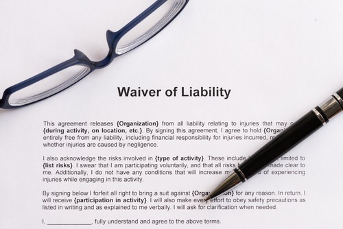 "document titled ""waiver of liability"" with glasses and pen lying on top of it"