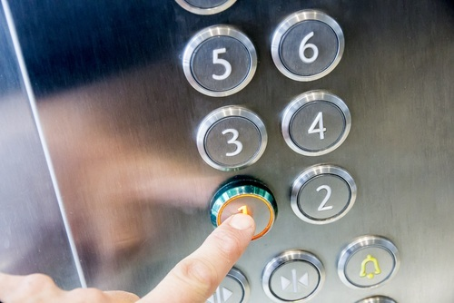 Person pressing an elevator button - elevator accident lawsuits can lead to money settlements for the victims