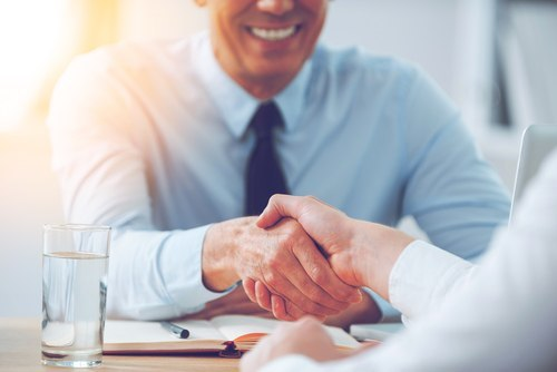 Smiling man in business suit shaking hand of a job applicant