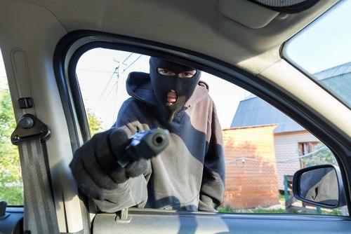 Masked man pointing gun into car