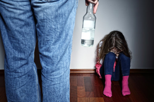 adult in front of child holding bottle of alcohol