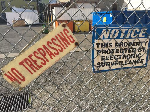 """""""no trespassing sign"""" on a chainlink fence - Penal Code 602 PC makes trespassing a crime in California"""
