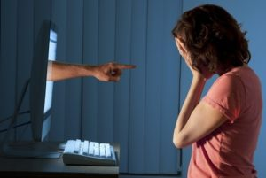 Finger-pointing projecting through computer at distressed woman