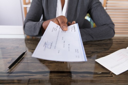 woman at desk handing over a paycheck