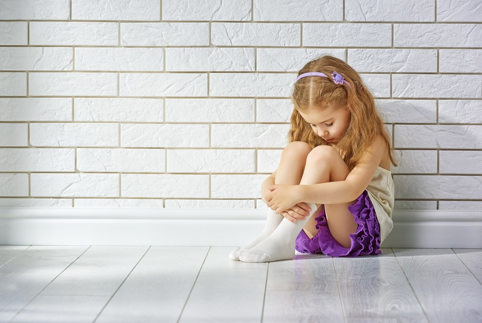 Young child sitting with head bowed - sexual assault on a child by a person in a position of trust is a serious crime in Colorado