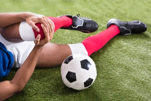 young soccer player laying on field clutching knee sports injuries at school can give rise to a claim for damages