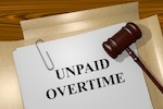 """paper that says """"unpaid overtime' and gavel"""