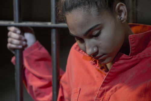 young female inmate inside of a jail cell - bringing contraband into a California jail or prison is a violation of Penal Code 4573.5 PC