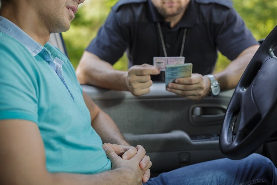 Driver pulled over with cop looking at license