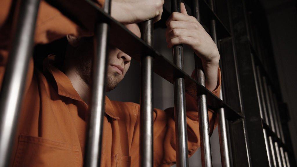 Man in orange jumpsuit behind bars