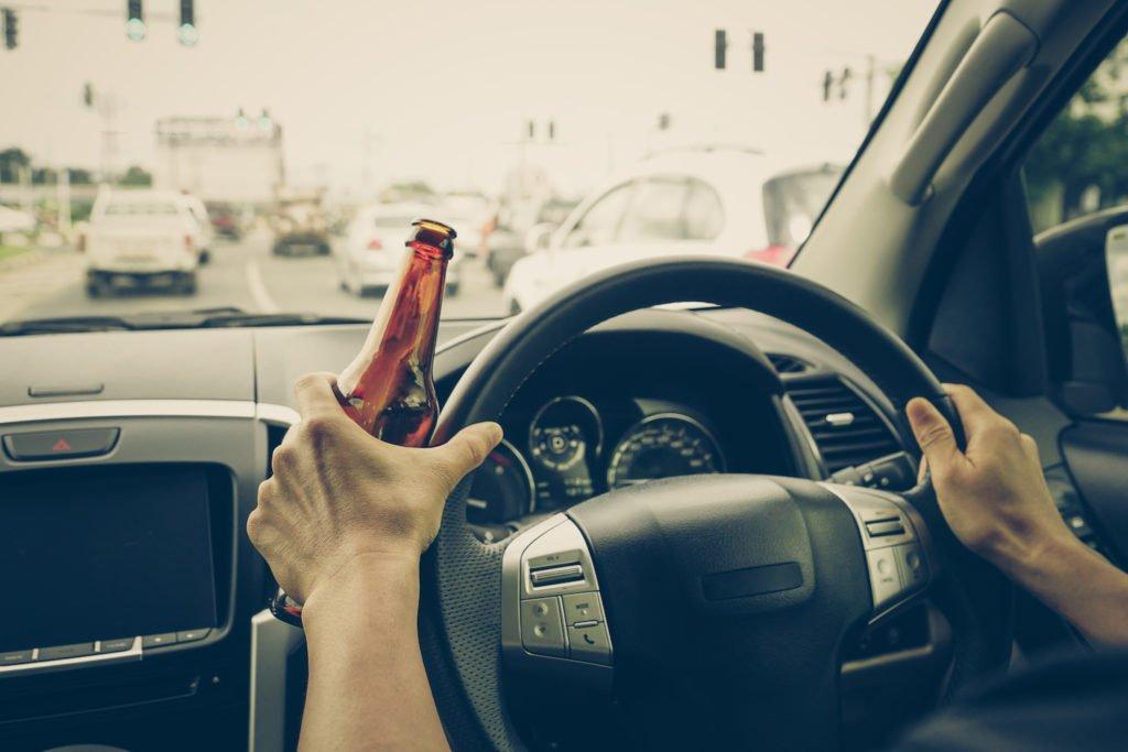 Hands on car wheel while holding beer bottle