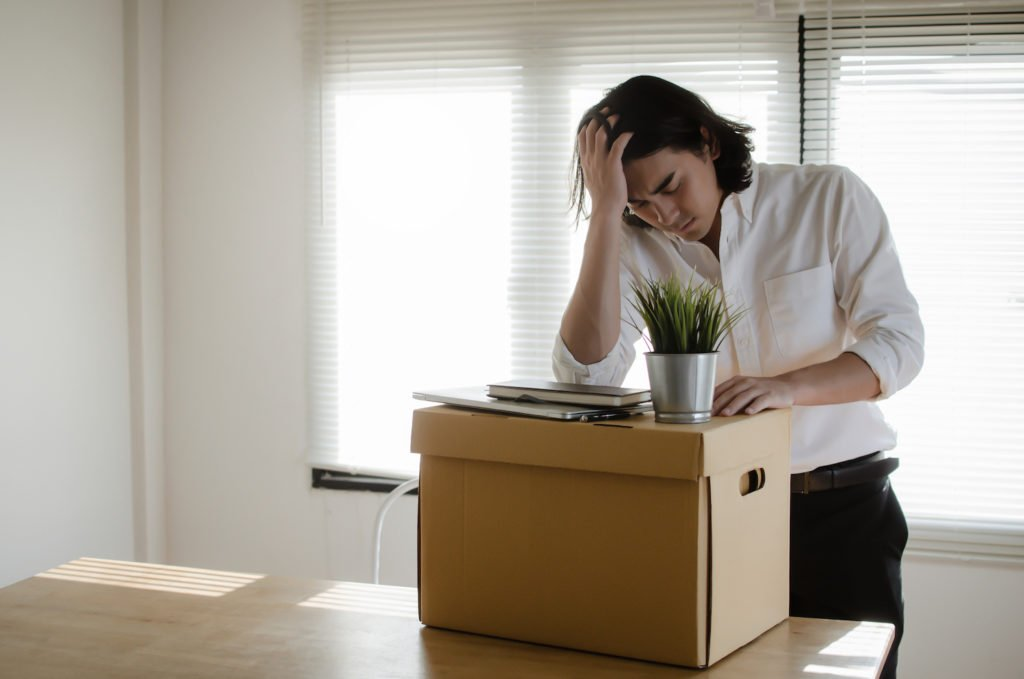 Fired worker packing up desk after being retaliated against for filing a workers' comp claim