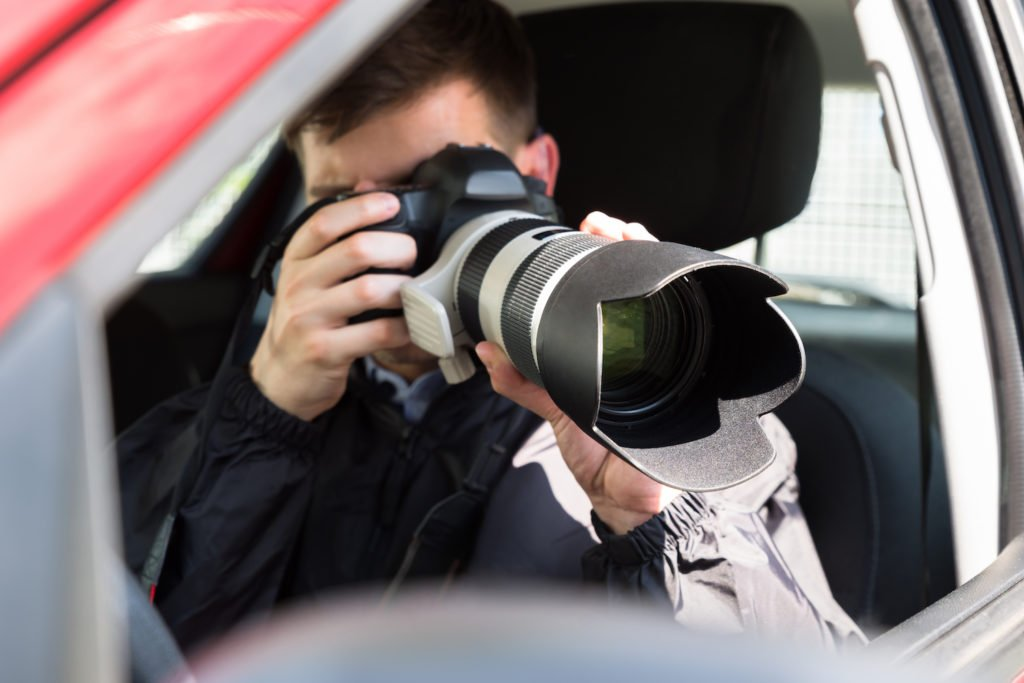 Private eye in car holding a telephoto lens