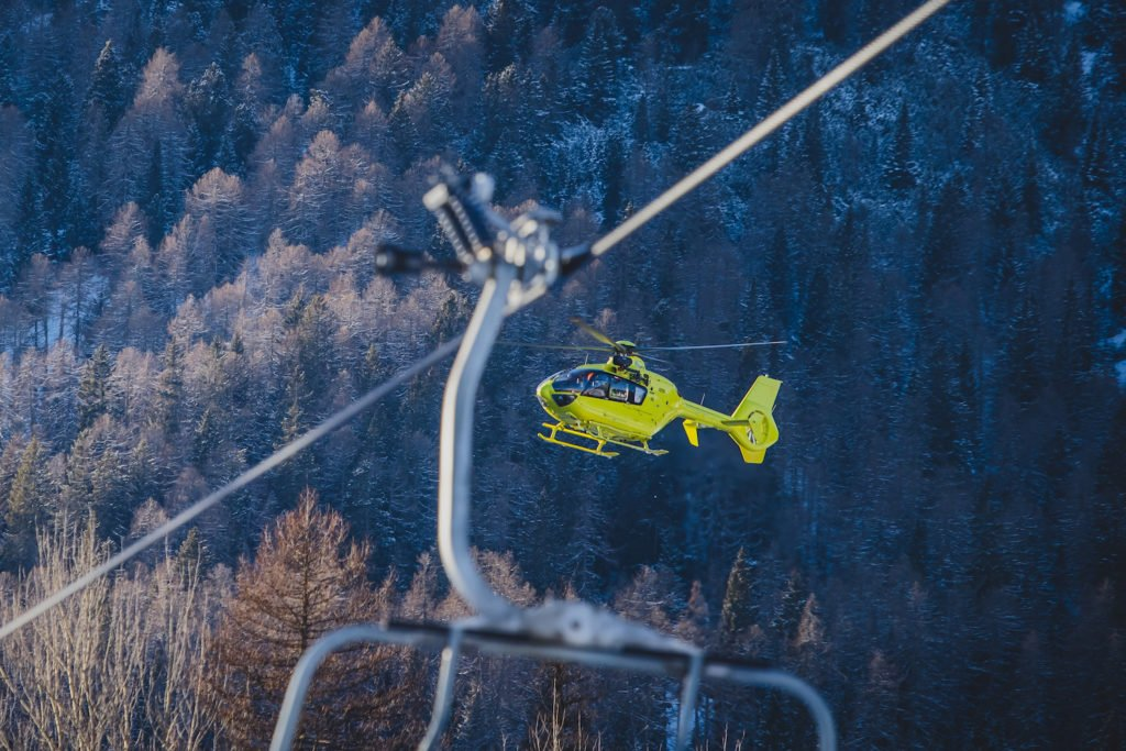 Helicopter flying to a ski lift against backdrop of mountains