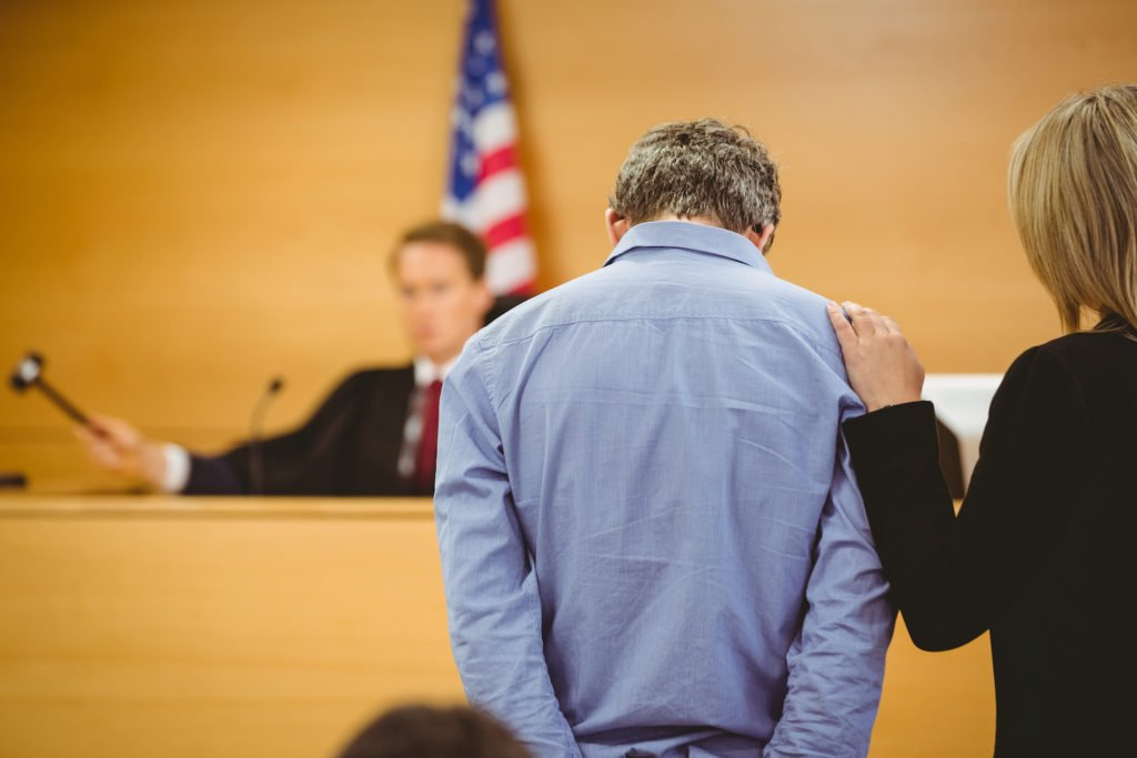 Defendant and his attorney before a judge holding a gavel
