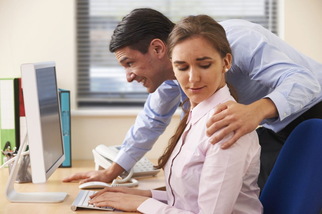 Male boss putting hand on shoulder of female employee at desk - our California employment law attorneys help clients to bring sexual harassment claims