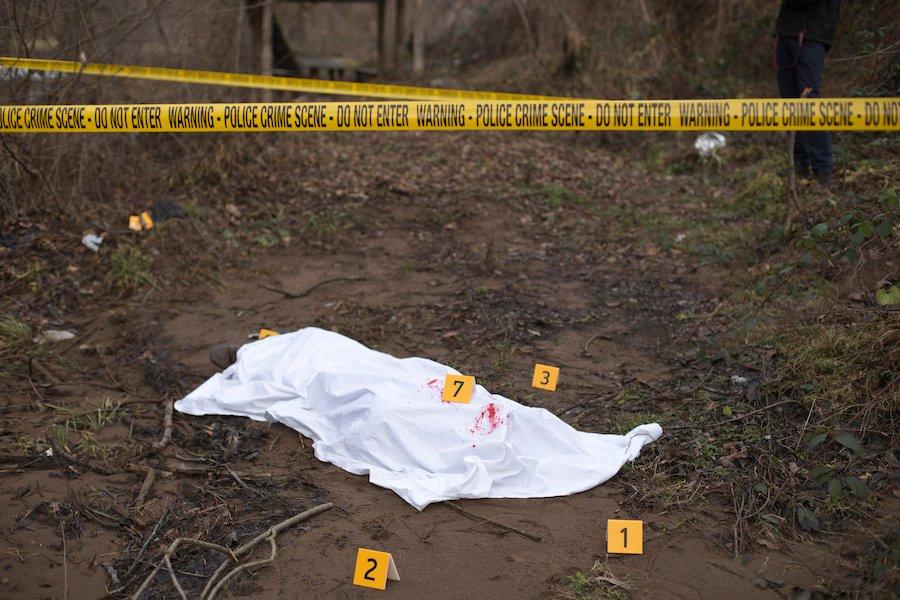 crime scene tape with sheet over body in ditch