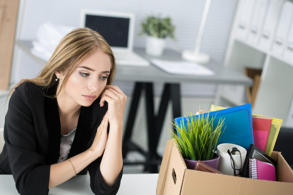 Fired employee next to box of belongings at old work desk