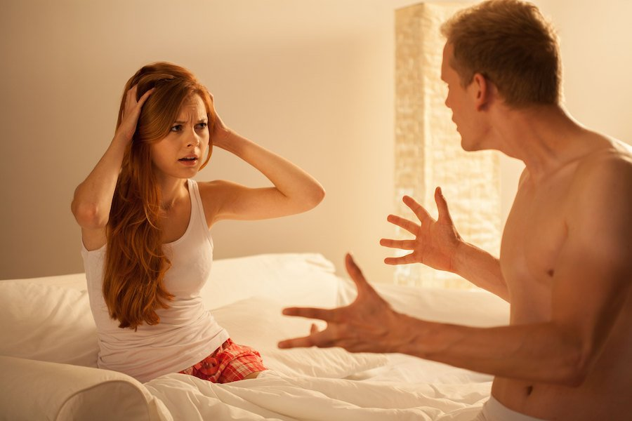Married couple in bed arguing
