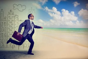 Man in businss suit leaping from work into beach