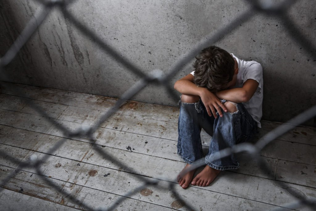Young person crouching in a detention facility