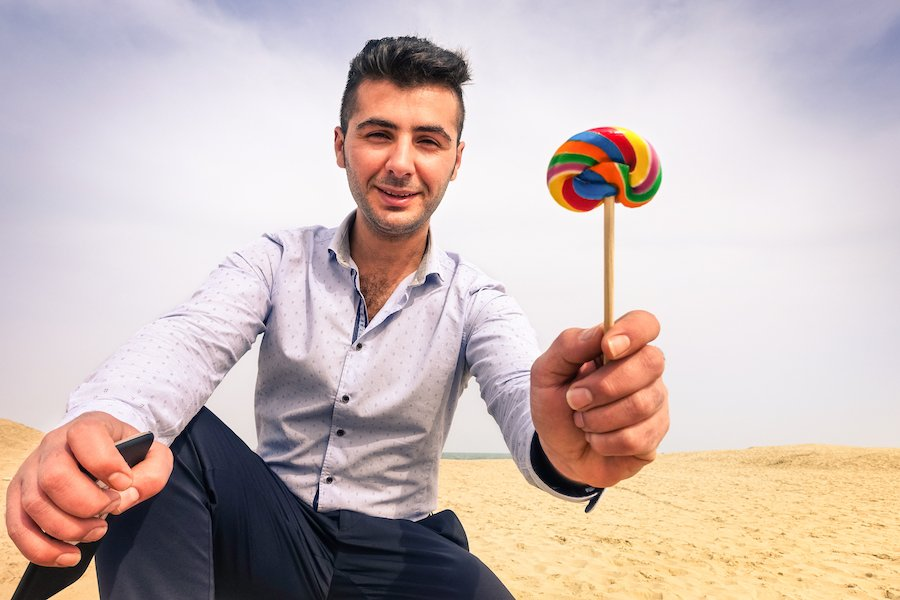 Man holding lollipop out to child behind the camera