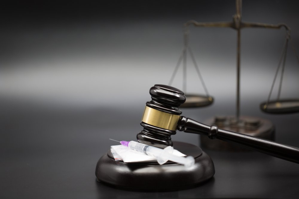 syringe and drugs by a judge's gavel