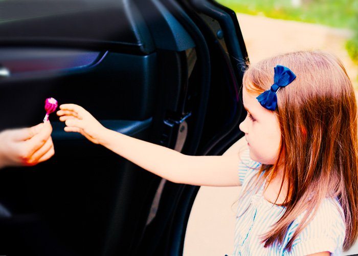 girl reaching out for a lollipop from a stranger in a car