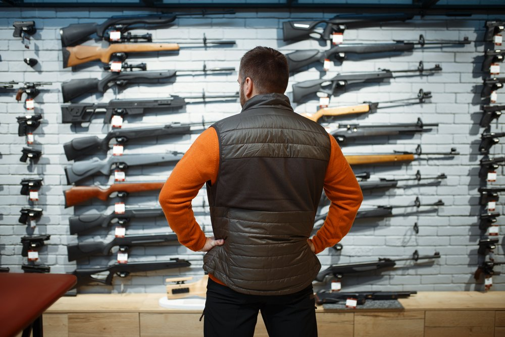 man looking at guns in a store