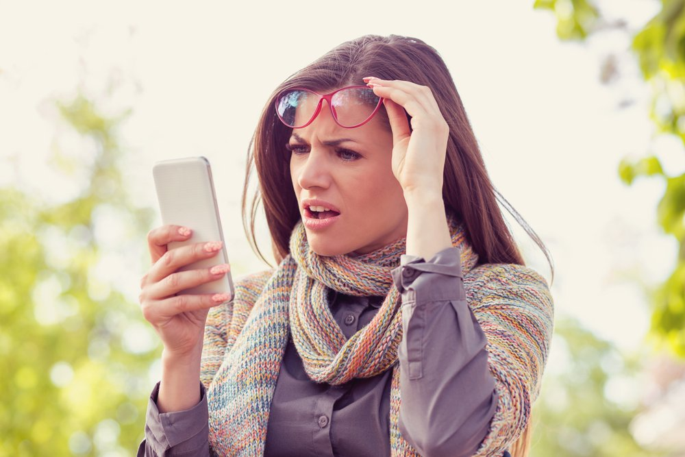 Woman shocked by what she is reading on her smartphone.
