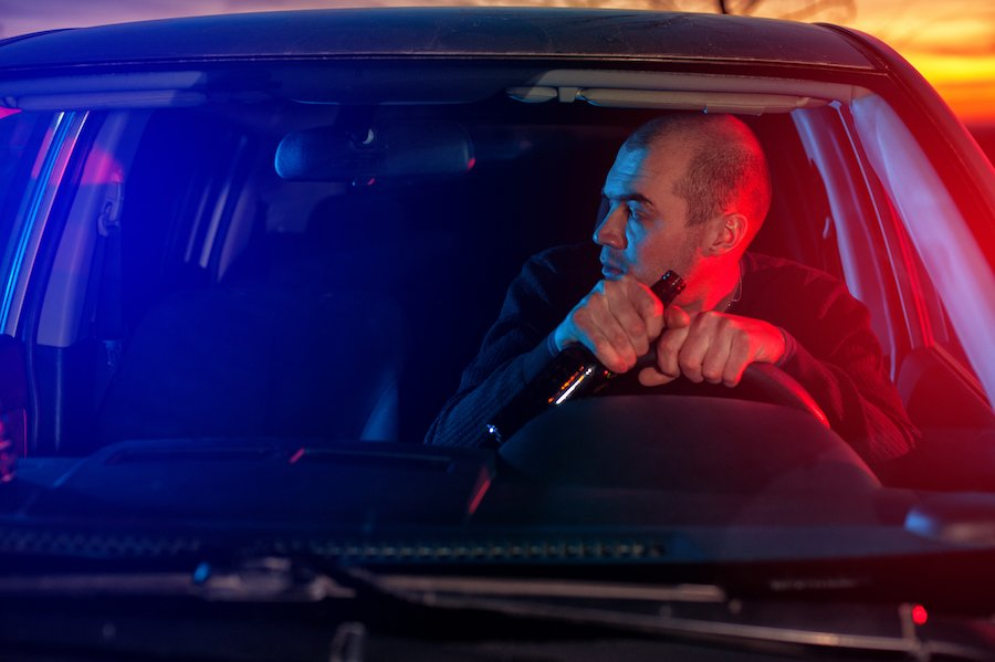 Man driving while holding beer with police lights behind him