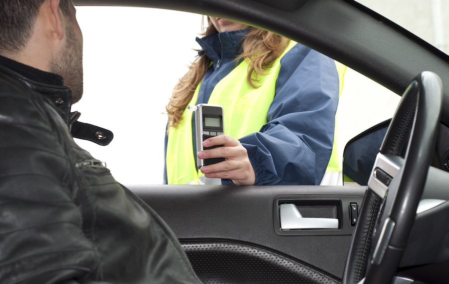 Police administering roadside breathalyzer test to DUI suspect behind the wheel
