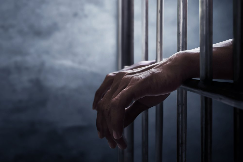 Inmate's hand extending out of a jail cell - a violation of Penal Code 653b PC can lead to up to 6 months in custody
