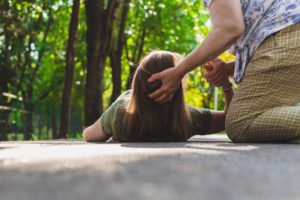 Woman having her head held up after fainting.